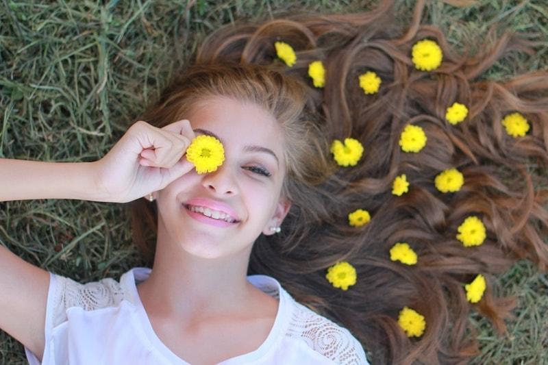 花を目に当てる女性