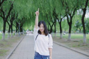 上を指さす女性